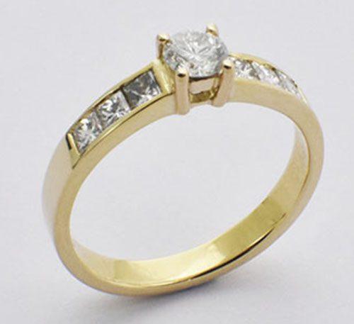 Anillo de compromiso en oro con diamante brillante de 0,25 Ct. y 2 diamantes princesa. Ref. 123-300