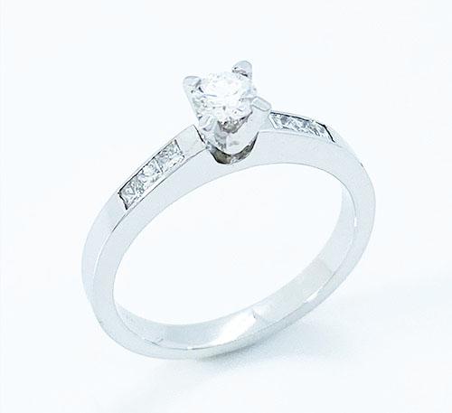 Anillo compromiso oro blanco con diamante brillante de 0,22 quilates y 6 princesa