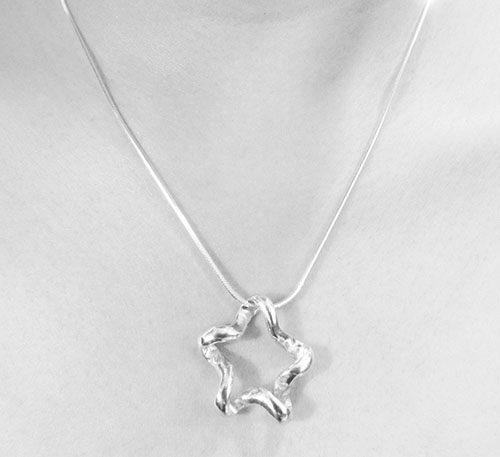 Dije de plata ley 0,950 de peso 5 gramos. Diseño en forma de lazo estrella.
